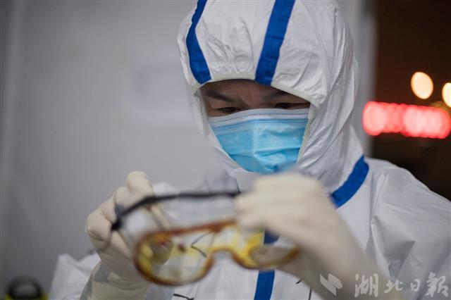 2月24日晚上,一位医疗队员正在护目镜内测涂抹碘酒防止镜片起雾