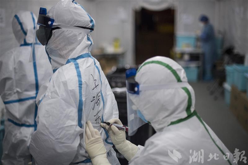 2月24日晚上,一位上海医疗队员在同伴的防护服上写上单位名称